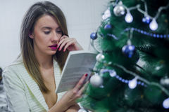 Dreaming young woman sitting chair and reading book in front of Christmas tree. Stock Image