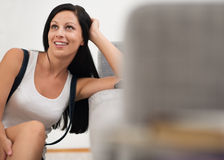 Dreaming young woman sitting on floor near couch Royalty Free Stock Photos