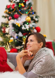 Dreaming young woman sitting near Christmas tree Stock Images