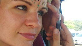 Dreamlike beautiful young woman is gluing to her forehead for the festival with the cutter knife rhinestones stock photography