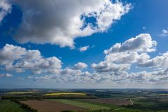 dreamlike blue sky with white sheep clouds over green and yellow fields royalty free stock photos