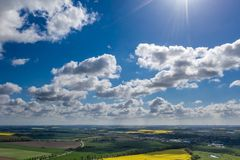 Dreamlike blue sky with white sheep clouds over green and yellow fields royalty free stock images