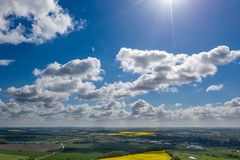 dreamlike blue sky with white sheep clouds over green and yellow fields stock photo