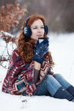 Dreamly young red-haired woman drinking a hot drink from a mug in the winter park. Stock Photography