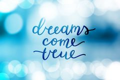 Dreams come true. Lettering on blurred background Stock Photos