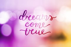 Dreams come true. Lettering on blurred background Royalty Free Stock Photo