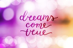 Dreams come true. Lettering on blurred background Stock Images