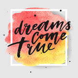 Dreams come true hand drawn lettering on watercolor splash on watercolor splash in red and yellow colors. Royalty Free Stock Image