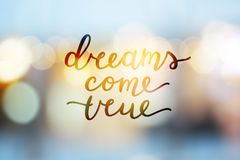 Dreams come true. Lettering on blurred background Stock Image