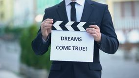 Dreams come true phrase on clapperboard in hands of producer, cinematography. Stock footage stock footage