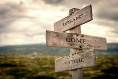 Dreams come true wooden signpost outdoors in nature. royalty free stock photography