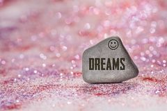 Dreams engrave on stone. On shiny red and purple glitter with bokeh background royalty free stock photos