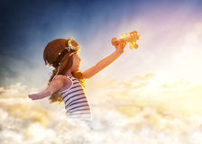 Dreams of flight. ! child playing with toy airplane against the sky at sunset Royalty Free Stock Image