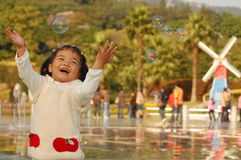 Dreams fly. Happy little Asian girl playing with colorful bubbles Stock Photo
