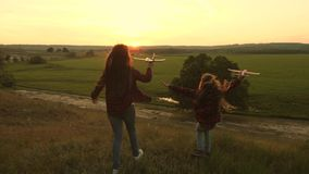 Dreams of flying. Happy childhood concept. Two girls play with a toy plane at sunset. Children on background of sun with. An airplane in hand. Silhouette of royalty free stock image
