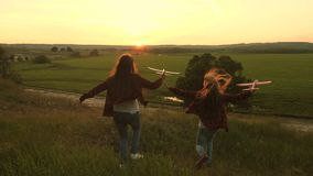 Dreams of flying. Happy childhood concept. Two girls play with a toy plane at sunset. Children on background of sun with. An airplane in hand. Silhouette of stock photo
