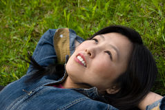 Dreams in the grass. Young attractive woman  relaxes in the park Royalty Free Stock Photography