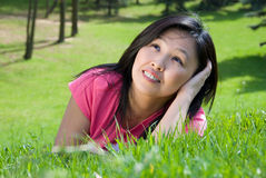 Dreams in the grass. Young attractive woman  relaxes in the park Royalty Free Stock Photos