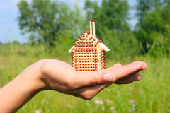 Dreams in hands. The match small house which is on a female hand, on a blossoming meadow Stock Images