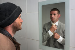 Dreams and hopes. Unemployed man looking in mirror and seeing aspirations of a better future Stock Photos