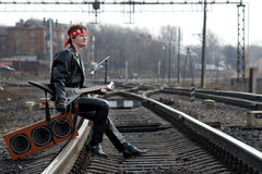 Dreams Of The Near Future. The young rock musician sits on the rail with his guitar and dreams about his future Stock Photo
