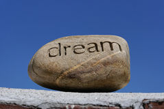 Dreams put on the shelf. A rock with the word dream inscribed in it  sits on top of a brick wall against a deep blue sky Stock Photography