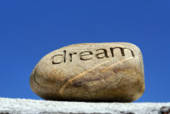 Dreams put to rest. Dreams put on the shelf, a rock with the word dream inscribed in it  sits on top of a brick wall against a deep blue sky Stock Images