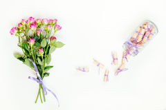 Dreams on a rolled paper and pink little roses. Dreams written on a pink rolled paper in a glass jar and fresh pink little roses. Flat lay on white background Royalty Free Stock Images