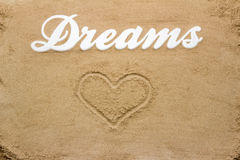 Dreams on the sandy beach. The sandy beach is the writing Dreams from wood. Including a heart drawn in the sand Royalty Free Stock Photo