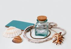 Dreams of sea vacation. Still life composition on white background with sea shells, beads necklace, glass bottle, paper ship and a craft paper notebook with Stock Image
