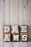 DREAMS sign made of wooden blocks on wooden background Stock Photos