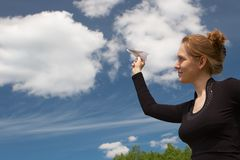 Dreams of the sky. Nice girl with paper plane in a hand on a background of the beautiful blue sky with clouds Stock Photo