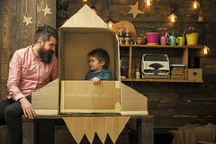 Dreams of space. Kid happy sit in cardboard hand made rocket. Boy play with dad, father, little cosmonaut sit in rocket. Made out of cardboard box. Rocket royalty free stock image