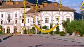 Dreams, summer. Children`s swing hover in the wind. Slow moshion. Dreams, summer. The family enjoys the summer, walks. The boy is riding on a swing. Slow stock video footage