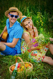 Dreams of a summer. Enamored young men with a guitar singing his beloved girlfriend. They are sitting together on a lawn on a sunny summer day. Love concept Royalty Free Stock Photography