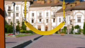 A yellow swing on steel chains pumps the wind on the playground. Slow motion. Dreams, summer. The family enjoys the summer, walks. The boy is riding on a swing stock video