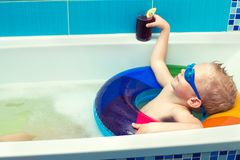 A little boy in goggles is floating in an inflatable circle in the bathroom and drinks juice. Dreams about summer. royalty free stock photos