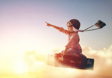 Dreams of travel. ! Child flying on a suitcase against the backdrop of a sunset Stock Photo