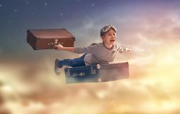 Dreams of travel. ! Child flying on a suitcase against the backdrop of sunset Stock Photos