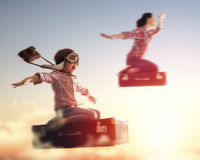 Dreams of travel!. Child girl and her mom flying on a suitcase against the backdrop of a sunset Stock Photos
