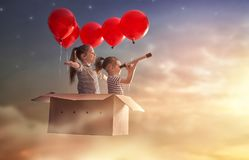 Dreams of travel. ! Two children are flying in cardboard box with air balloons Royalty Free Stock Images