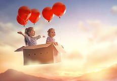 Dreams of travel. ! Two children are flying in cardboard box with air balloons Stock Photos