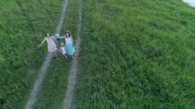Dreams of travel, happy family with globe in hands raised up on meadow in drone view. Dreams of travel, happy family with globe in hands raised up on green stock footage