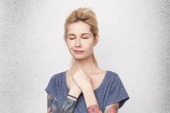 Dreams will come true! Portrait of young attractive blonde woman with pierced nose closed her eyes and dream about new life. Isolated over studio white wall royalty free stock images