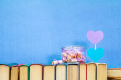 Dreams written on pink rolled paper in glass jar. Valentines day concept. Dreams written on a pink rolled paper in a glass jar, blue paper heart, violet paper Stock Images