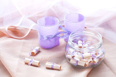 Dreams written on a white rolled paper in a glass jar and two aromatic candles in glass candlesticks with lavender paper Royalty Free Stock Photos