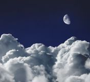 Dreamscape. Cumulus clouds shot from a high altitude against an indigo blue sky with the moon above Stock Images