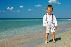 Free Dreamy Baby Boy Stands In Surf On Sea Beach Stock Images - 26938314