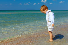 Dreamy baby boy stands in surf on sea beach Stock Photos