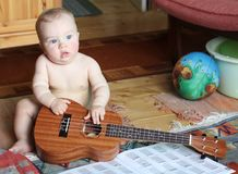 Dreamy baby learns to play ukulele at home. Tutorial chords Stock Image